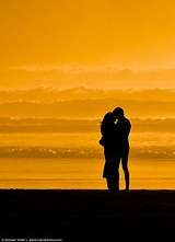 Lovers embracing on the beach at sundown - photo by mikebaird at Flickr